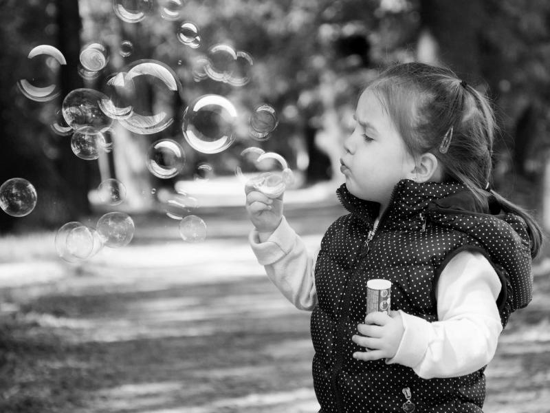 Female child blowing bubbles in a path lined with trees